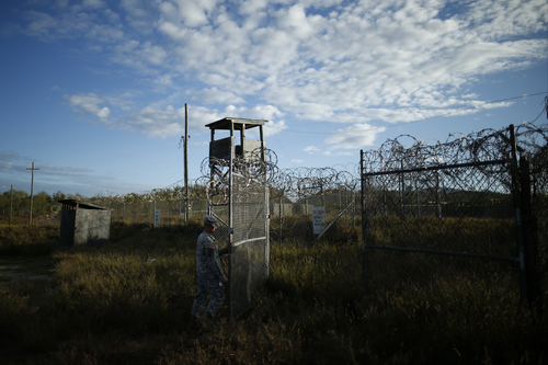In this photo reviewed by the U.S. military, a soldier closes the gate at the now abandoned Camp X-Ray, which was used as the first detention facility for al-Qaida and Taliban militants who were captured after the Sept. 11 attacks at Guantanamo Bay Naval Base, Cuba, Thursday, Nov. 21, 2013.  Detainees were housed in open air pens until the completion of Camp Delta in April 2002. Many detainees at Guantanamo Bay may be closer to heading home under a bipartisan deal reached in Congress that gives President Barack Obama a rare victory in his fight to close the prison for terror suspects. (AP Photo/Charles Dharapak)
