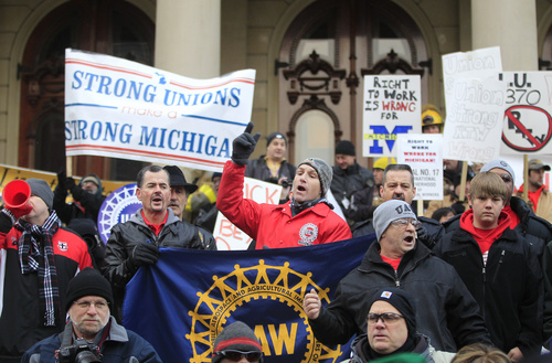 FILE - In this Dec. 11, 2012 file photo some of the thousands that gathered for a rally protest against the passage of right-to-work legislation outside the State Capitol in Lansing, Mich. Buoyed by recent successes in the Midwest, supporters of right-to-work laws are targeting at least three states in 2014 with measures that could curb union powers by ending their ability to collect mandatory bargaining fees. Their strategy, appealing to voters instead of relying on potentially reluctant governors to enact laws passed by legislators, could avoid a redo of the massive union-led protests that clogged some Midwestern capitols where Republicans recently enacted other anti-union proposals. (AP Photo/Carlos Osorio, File)