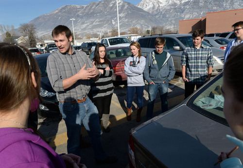 Francisco Kjolseth  |  The Salt Lake Tribune Science teacher Matthew Rytting takes physics into the parking lot as he has his Pleasant Grove High students weigh his car using four pieces of paper by applying the principle of force is equal to pressure times area.  High School graduation rates were released on Tuesday, Dec. 17, 2013, and the Alpine District saw a significant rise in graduation rates which has been credited in part to teachers making adjustments throughout the year by knowing how all their kids are performing regularly.