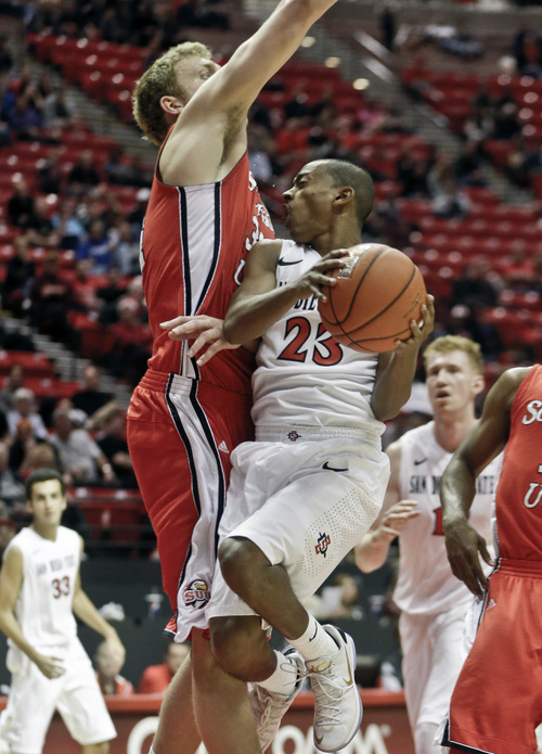 San Diego State guard Kibret Woldemichael takes a hard foul from Southern Utah center Cal Hanks during the second half of an NCAA college basketball game, Wednesday, Dec. 18, 2013, in San Diego. (AP Photo/Lenny Ignelzi)