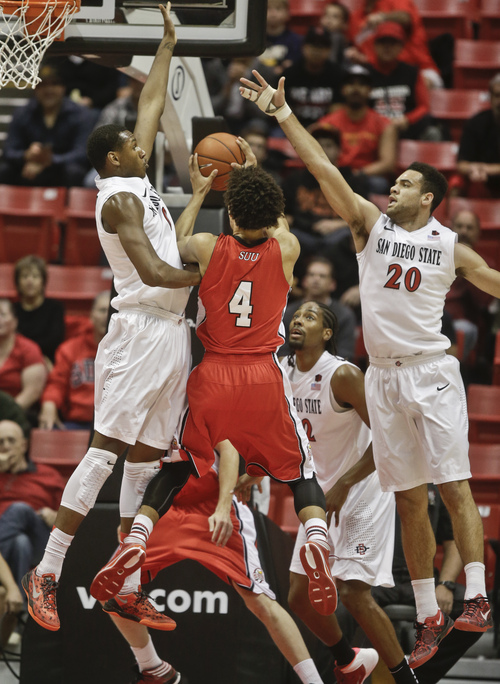 Southern Utah guard Trey Kennedy has his shot blocked by San Diego State center Skylar Spencer, left, as he gets caught between Spencer and JJ O'Brien while driving during the first half of an NCAA college basketball game Wednesday, Dec. 18, 2013, in San Diego. (AP Photo/Lenny Ignelzi)