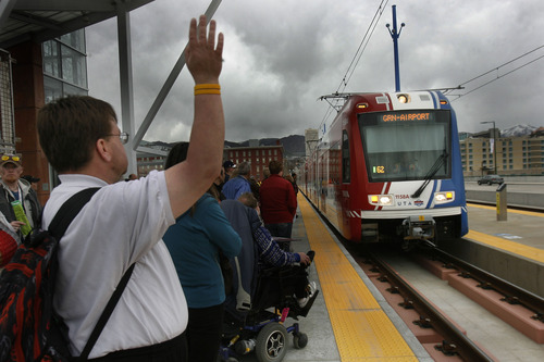 Scott Sommerdorf   |  The Salt Lake Tribune Riders prepare to board the TRAX train at North Temple Bridge Station as it heads west on North Temple on its way to the airport on Saturday, April 13, 2013.