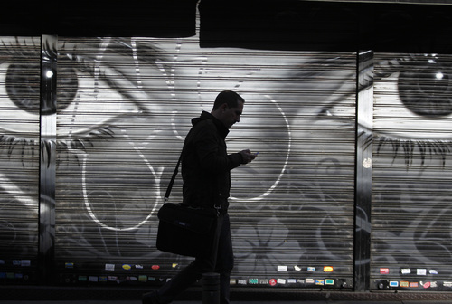 FILE - In this Thursday, Oct. 31, 2013, file photo, a man looks at his cellphone as he walks on the street in downtown Madrid. The National Security Agency tracks the locations of nearly 5 billion cellphones every day overseas, including those belonging to Americans abroad, The Washington Post reported Wednesday, Dec. 4, 2013. Such data means the NSA can track the movements of almost any cellphone around the world, and map the relationships of the cellphone user. (AP Photo/Francisco Seco, File)