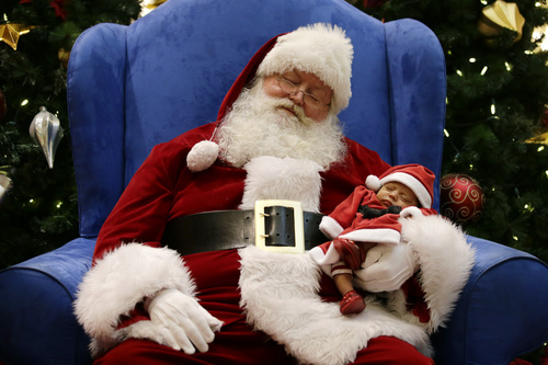 Dressed as Santa Claus, Mark Tate pretends to sleep as he poses for photos with 4-week-old Leilani Mejico at a mall in Cerritos, Calif. on Tuesday, Dec. 17, 2013. (AP Photo/Jae C. Hong)