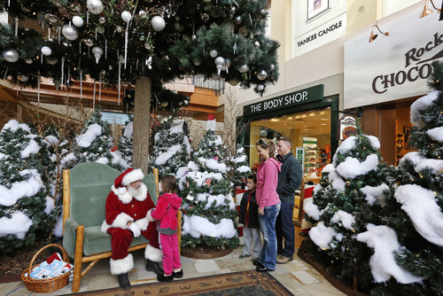 Capri Nielson, 5, is greeted by a man dressed as Santa Claus, as her parents Mike and Melissa, and brother Miles, 6, watch, at the Wonderland House inside Flatirons Crossing Mall, in Broomfield, Colo. on Wednesday, Dec. 18, 2013. (AP Photo/Brennan Linsley)