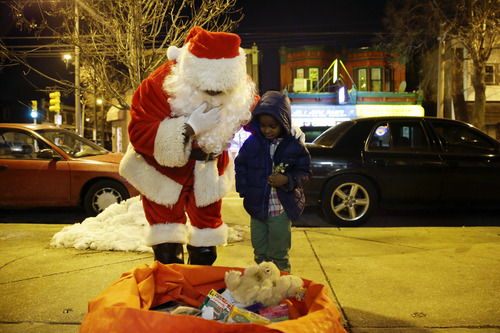 Paul Moore, left, dressed as Santa Claus, looks over a bag of toys with Dante Wright, 5, as Moore hands out holiday gifts to children at the Philadelphia Police Department's 12th district station in Philadelphia on Wednesday, Dec. 18, 2013. (AP Photo/Matt Slocum)