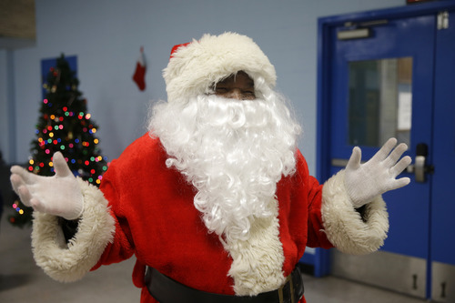 Paul Moore, dressed as Santa Claus, holds his hands in the air after he handed out holiday gifts to children at the Philadelphia Police Department's 12th district station, Wednesday, Dec. 18, 2013, in Philadelphia. (AP Photo/Matt Slocum)