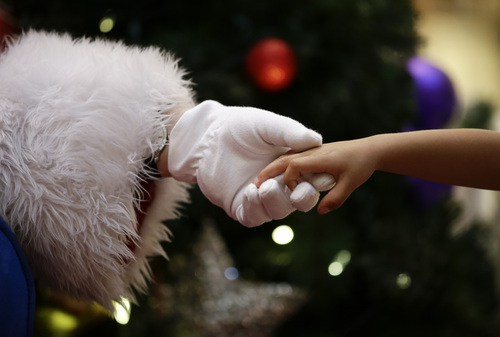 Dressed as Santa Claus, Mark Tate, left, holds the hand of Emmitt Lopez at a mall on Tuesday, Dec. 17, 2013, in Cerritos, Calif. (AP Photo/Jae C. Hong)