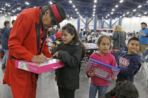 """Pancho Claus, portrayed by Richard Reyes, autographs gifts at a charity holiday event Saturday, Dec. 14, 2013, in Houston. """"For these diverse times, it's important for children to see Santa in all these different forms,"""" Reyes said. (AP Photo/Pat Sullivan)"""