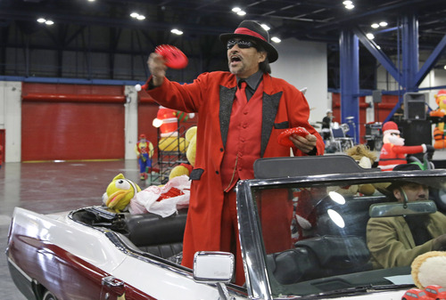 Pancho Claus throws presents as he arrives at a charity holiday event in a low-rider Saturday, Dec. 14, 2013, in Houston. The Tex-Mex Santa grew out of  the Chicano civil rights movement in the late 1970s and early 1980s and is sometimes referred to as Santa Claus' cousin from the South Pole. (AP Photo/Pat Sullivan)