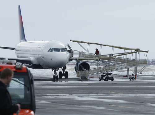 A Provo airport officials boards a Delta plane as it sits on the background at the Provo Airport on December 19, 2013 in Provo, Utah. Several Delta flight were diverted and landed at the Provo Airport after the Salt Lake City a Airport was closed standing several hundred passengers.  (Photo by George Frey     Special to the Tribune)