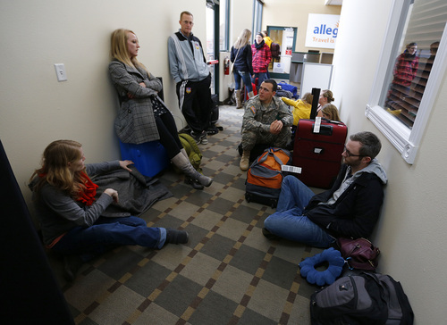 Passengers stand and sit on the floor at the Tac Air terminal after their flights were diverted to Provo at the Provo Airport on December 19, 2013 in Provo, Utah. Several Delta flight were diverted and landed at the Provo Airport after the Salt Lake City a Airport was closed standing several hundred passengers.  (Photo by George Frey     Special to the Tribune)