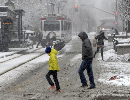Al Hartmann     The Salt Lake Tribune People slog and slide across Main Street in Salt Lake City during the heavy, wet snow falling Thursday Dec. 19, 2013.