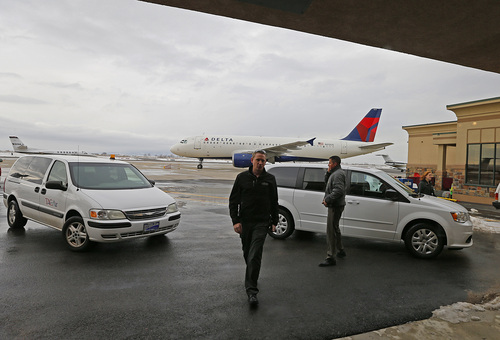 Pilots walk into the terminal as a Delta plane sit on the ground at the Provo Airport on December 19, 2013 in Provo, Utah. Several Delta flight were diverted and landed at the Provo Airport after the Salt Lake City a Airport was closed standing several hundred passengers.  (Photo by George Frey     Special to the Tribune)
