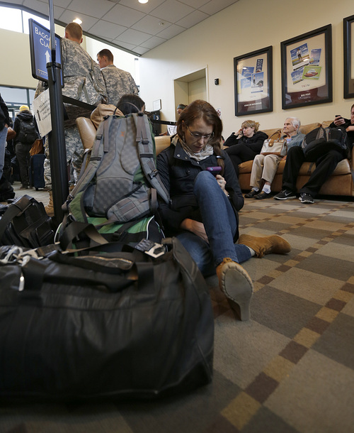 Passenger Holly Horan on her way to Phoenix sit son the floor with other passengers at the Tac Air terminal after her flight was diverted to Provo at the Provo Airport on December 19, 2013 in Provo, Utah. Several Delta flight were diverted and landed at the Provo Airport after the Salt Lake City a Airport was closed standing several hundred passengers.  (Photo by George Frey     Special to the Tribune)