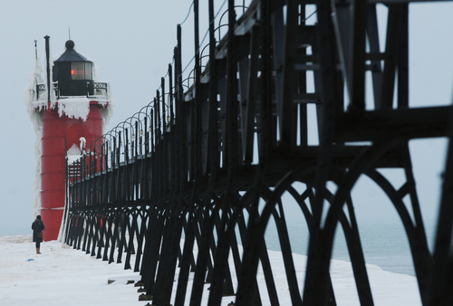 A woman explores an ice-covered pier at the South Haven Lighthouse Saturday, Dec. 21, 2013, in South Haven, Mich. (AP Photo/The Herald-Palladium, Don Campbell)