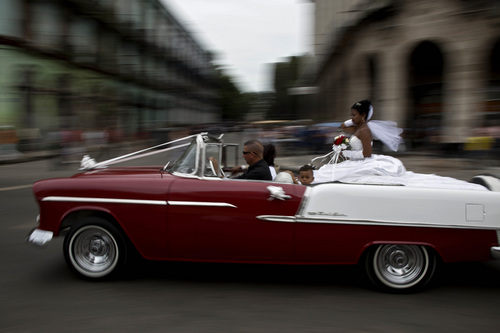 "A bride is driven to her wedding ceremony in a classic American car in Havana, Cuba, Thursday, Dec. 19, 2013. In Cuba, time is in the eye of the beholder. After a half century of Communism the days still pass slowly for many islanders. Others say the pace of life has quickened considerably in the three years since President Raul Castro admonished Cubans to embrace economic reforms ""without haste, but without pause."" (AP Photo/Ramon Espinosa)"