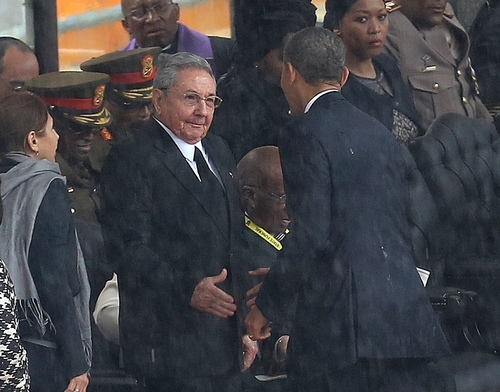 "FILE - In this Tuesday Dec. 10, 2013 file photo, U.S. President Barack Obama shakes hands with Cuban President Raul Castro, as it rains during a memorial service for former South African President Nelson Mandela, at the FNB Stadium in Soweto, South Africa. Fidel Castro says his brother Raul introduced himself to Obama in English, telling him, ""Mr. President, I'm Castro,"" as the two leaders shook hands. The Dec. 10 handshake set off speculation in the U.S. and Cuba about whether it signaled a warming of ties between the two nations after decades of animosity. U.S. and Cuban officials dismissed that, calling the handshake a mere courtesy. (AP Photo/File) SOUTH AFRICA OUT"