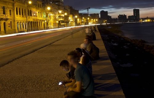 A man uses his smart phone as car lights leave traces as they drive along the Malecon in Havana, Cuba, Thursday, Dec. 19, 2013. In many parts of Havana, the cityscape is changing rapidly. Along once darkened streets, pedestrians now walk through the neon glow of signs advertising new bars, restaurants and rooms for rent. On the waterfront, a crumbling pier has been razed and a gleaming microbrewery is set to open its doors. (AP Photo/Ramon Espinosa)