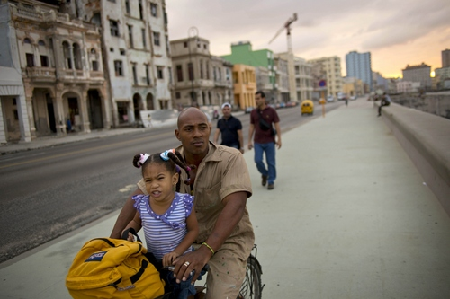 A worker and his daughter make their way home on a bike in Havana, Cuba, Thursday, Dec. 19, 2013. For the restless, change is coming too slowly. Yes, they can travel and buy property, but they want more: more money, more opportunity, more political freedom. The Communist Party is still the only legal political party on the island, and officials say that's not up for debate. (AP Photo/Ramon Espinosa)