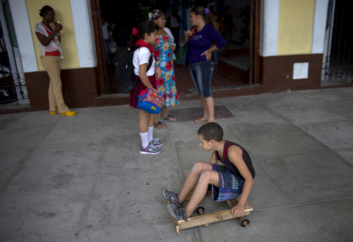 A child rides on a scooter made from scraps of wood in Havana, Cuba, Thursday, Dec. 19, 2013. For many islanders, the days still pass slowly under an enervating sun. After a half century of Communism, they see time frozen in the facades of crumbling colonial mansions, the chrome of 1950s automobiles and the face of a stopped airport clock. (AP Photo/Ramon Espinosa)