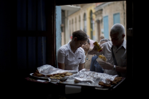 People line up to buy empanadas at a small private business in Havana, Cuba, Thursday, Dec. 19, 2013. Many Cubans say life has speeded up since Raul Castro took over the presidency in 2006, when Fidel was stricken with an intestinal disease that nearly killed him. Raul quickly legalized computers and cell phones and removed restrictions on Cubans entering tourist hotels, but he waited three years to announce more fundamental changes, including an embrace of limited forms of free market capitalism. (AP Photo/Ramon Espinosa)