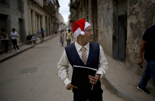Nino Torres, a waiter at a private restaurant, wears a Santa Claus hat as he looks for customers in the streets of Old Havana, Cuba, Thursday, Dec. 19, 2013. A smattering of Christmas trees and wreaths hang in private businesses and homes, as holiday displays have become more common in a country that was officially atheist for decades. (AP Photo/Ramon Espinosa)