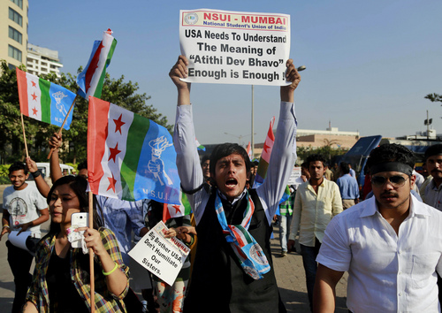 """A member of the National Students Union of India (NSUI), the student wing of India's ruling Congress party, shouts slogans during a protest outside the U.S. consulate in Mumbai, India, Friday, Dec. 20, 2013. India's Information Minister Manish Tewari lashed out at the United States on Friday and demanded an apology for the treatment and arrest of Devyani Khobragade, India's deputy consul general in New York, saying America cannot behave """"atrociously"""" and get away with it. Meaning of """"Atithi Dev Bhavo"""" on placard is """"Guest is God"""". (AP Photo/Rafiq Maqbool)"""