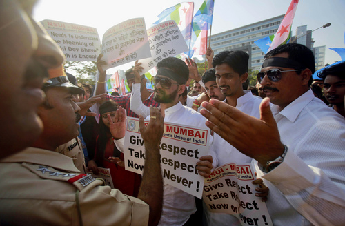 """Indian policemen stop a group of the student wing of ruling Congress party, National Students Union of India (NSUI), during a protest outside the U.S. consulate in Mumbai, India, Friday, Dec. 20, 2013. India's Information Minister Manish Tewari lashed out at the United States on Friday and demanded an apology for the treatment and arrest of Devyani Khobragade, India's deputy consul general in New York, saying America cannot behave """"atrociously"""" and get away with it. (AP Photo/Rafiq Maqbool)"""