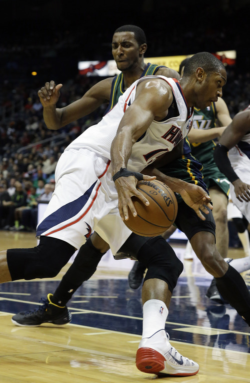 Atlanta Hawks center Al Horford, foreground, drives against Utah Jazz small forward Jeremy Evans in the second half of an NBA basketball game on Friday, Dec. 20, 2013, in Atlanta. (AP Photo/John Bazemore)