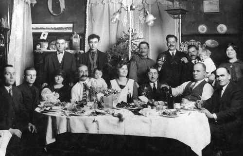 Photo Courtesy Utah State Historical Society  Mr. and Mrs. Gregory Halles, their daughter Athena and son John standing behind Mr. Halles, and other friends, in 1923 at a baptismal dinner at Christmas time in Salt Lake City.   Front Row, Left to Right: Unknown, George Coucourakis, Irene Rondas (Baby), Georgia Markakis, Gregory Halles, Athena Halles, Mary Halles, Unknown, Alex Halles, Mike Papadakis. Back Row: Nick Halles, John Halles, Theona, Unknown, Mr. Papais, Kathryn, Wife Stamatina.