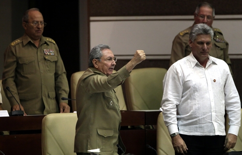"""Cuba's President Raul Castro, center left, with a raised fist shouts, """"Long live Fidel, long live the combative spirit of Fidel, long live the Revolution,"""" accompanied by Vice President Miguel Diaz-Canel, right, Army Corps Gen. Alvaro Lopez Miera, back right, and Cuban Armed Forces Minister Leopoldo Cintras Frias, at the close of the of a twice-annual legislative sessions, at the National Assembly  in Havana, Cuba, Saturday, Dec. 21, 2013. (AP Photo/Cubadebate, Ismael Francisco)"""