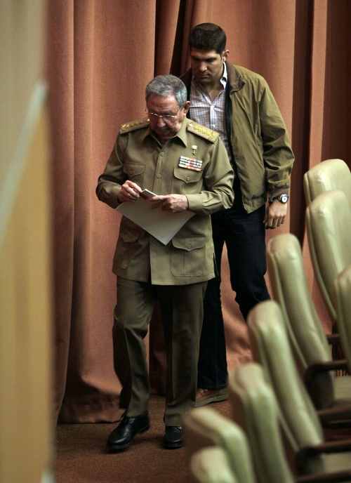 """Cuba's President Raul Castro walks towards a podium to deliver his speech at the closing of the second day of a twice-annual legislative sessions, at the National Assembly in Havana, Cuba, Saturday, Dec. 21, 2013. Castro issued a stern warning to entrepreneurs pushing the boundaries of Cuba's economic reform, saying """"those pressuring us to move faster are moving us toward failure."""" Castro is followed by his personal assistant and grandson, Raul Guillermo Rodriguez Castro. (AP Photo/Cubadebate, Ismael Francisco)"""