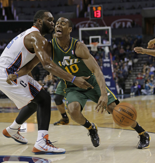 Utah Jazz's Alec Burks, right, is fouled by Charlotte Bobcats' Al Jefferson, left, during the first half of an NBA basketball game in Charlotte, N.C., Saturday, Dec. 21, 2013. (AP Photo/Chuck Burton)