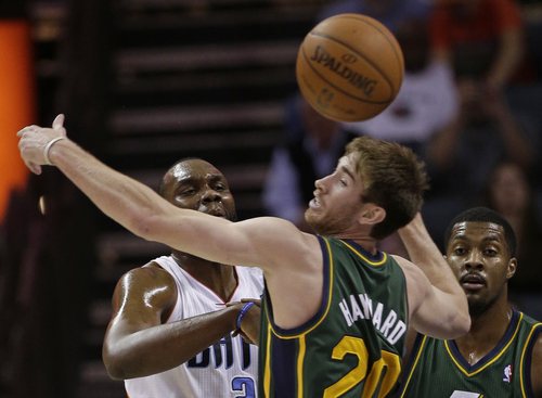 Charlotte Bobcats' Al Jefferson, left, passes the ball as he is trapped by Utah Jazz's Alec Burks, center, and Derrick Favors, right, during the first half of an NBA basketball game in Charlotte, N.C., Saturday, Dec. 21, 2013. (AP Photo/Chuck Burton)