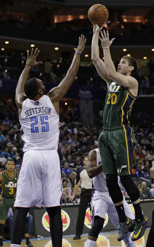Utah Jazz's Gordon Hayward (20) shoots over Charlotte Bobcats' Al Jefferson (25) during the first half of an NBA basketball game in Charlotte, N.C., Saturday, Dec. 21, 2013. The Jazz won 88-85. (AP Photo/Chuck Burton)