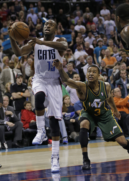 Charlotte Bobcats' Kemba Walker (15) drives past Utah Jazz's Trey Burke (3) during the second half of an NBA basketball game in Charlotte, N.C., Saturday, Dec. 21, 2013. The Jazz won 88-85. (AP Photo/Chuck Burton)