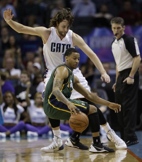 Utah Jazz's Trey Burke, front, tries to move past Charlotte Bobcats' Josh McRoberts, back, during the second half of an NBA basketball game in Charlotte, N.C., Saturday, Dec. 21, 2013. The Jazz won 88-85. (AP Photo/Chuck Burton)