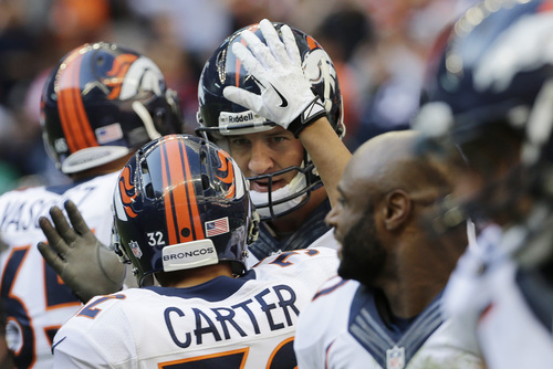 Denver Broncos' Peyton Manning, center, celebrates with teammates after he threw a touchdown pass against the Houston Texans during the third quarter of an NFL football game on Sunday, Dec. 22, 2013, in Houston. The touchdown was his 51st of the season. (AP Photo/David J. Phillip)