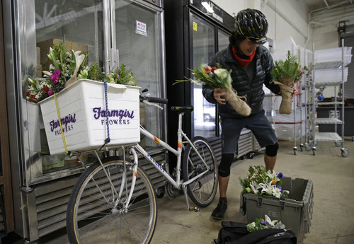 In this Dec. 19, 2013, Ian Kizu-Blair, with Farmgirl Flowers, drops off a shipment to the Good Eggs warehouse in San Francisco. New online services are letting consumers buy fruits, vegetables, meats and artisan foods directly from local farmers and producers. Buyers can have their orders delivered or retrieve them at local pickup spots. These virtual farmers markets are changing the way people buy groceries and creating new markets for small farmers, ranchers, bakers and other food makers. (AP Photo/Eric Risberg)
