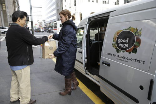 In this Dec. 18, 2013 photo, Good Eggs community dispatcher Vanessa Casey, right, hands an order to a Financial District customer in San Francisco. New online services are letting consumers buy fruits, vegetables, meats and artisan foods directly from local farmers and producers. Buyers can have their orders delivered or retrieve them at local pickup spots. These virtual farmers markets are changing the way people buy groceries and creating new markets for small farmers, ranchers, bakers and other food makers. San Francisco-based Good Eggs has built a fast-growing business connecting foodies and farmers in Northern California. (AP Photo/Eric Risberg)