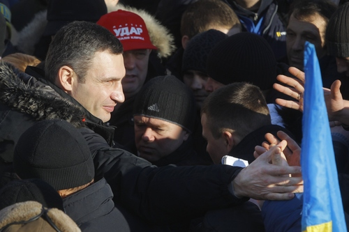 Ukrainian lawmaker and chairman of the Ukrainian opposition party Udar (Punch), WBC heavyweight boxing champion Vitali Klitschko is greeted by Pro-European Union activists during a rally in the Independence Square in Kiev, Ukraine, Sunday, Dec. 22, 2013. Protesters in Kiev are demanding President Viktor Yanukovych's resignation over his decision to ditch a pact with the European Union in favor of closer ties with Russia. (AP Photo/Sergei Grits)