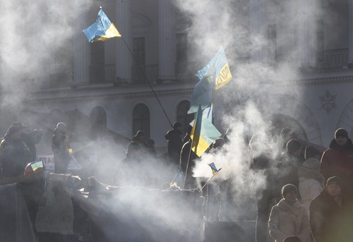 Pro-European Union activists warm themselves by a fire prior a rally in Independence Square in Kiev, Ukraine, Sunday, Dec. 22, 2013. Protesters in Kiev are demanding President Viktor Yanukovych's resignation over his decision to ditch a pact with the European Union in favor of closer ties with Russia. (AP Photo/Sergei Chuzavkov)