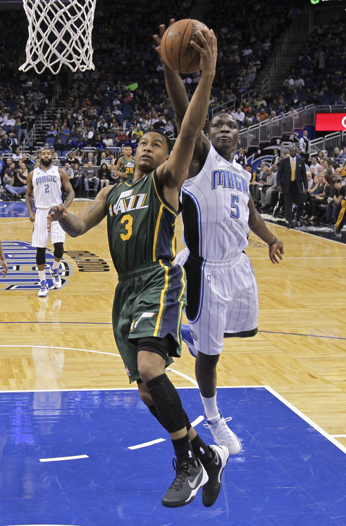 Orlando Magic's Victor Oladipo (5) blocks a shot by Utah Jazz's Trey Burke (3) during the first half of an NBA basketball game in Orlando, Fla., Wednesday, Dec. 18, 2013. (AP Photo/John Raoux)