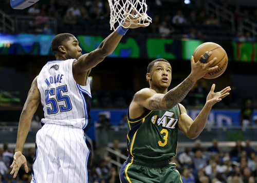 Utah Jazz's Trey Burke (3) goes around Orlando Magic's E'Twaun Moore (55) to shoot during the second half of an NBA basketball game in Orlando, Fla., Wednesday, Dec. 18, 2013. Utah won the game 86-82. (AP Photo/John Raoux)