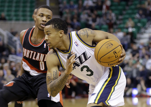 Utah Jazz's Trey Burke (3) drives as Portland Trail Blazers' Damian Lillard (0) stands by in the first quarter during an NBA basketball game Monday, Dec. 9, 2013, in Salt Lake City.  (AP Photo/Rick Bowmer)
