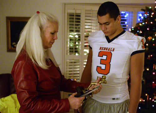 Rick Egan    The Salt Lake Tribune   Colleen Lindstrom looks at her grandson, Brighton High football star, Osa Masina's trophy's, Wednesday, December 18, 2013. Brighton RB/LB Osa Masina has been selected as MVP of the first-ever All-Tribune team.