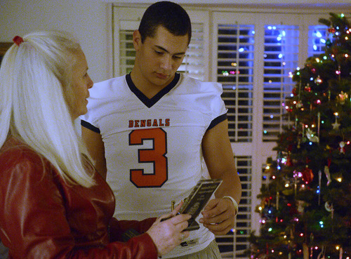 Rick Egan  | The Salt Lake Tribune   Colleen Lindstrom looks at her grandson, Brighton High football star, Osa Masina's trophy's, Wednesday, December 18, 2013. Brighton RB/LB Osa Masina has been selected as MVP of the first-ever All-Tribune team.