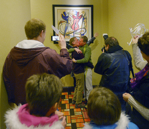 Steve Griffin  |  The Salt Lake Tribune   Rev. Monica Hall, of Trinity Presbyterian Church in Ogden, holds up her hands up as she announces Mark Marinan and Jeff poor officially married at the Hampton Inn Suites in Ogden, Utah Monday, December 23, 2013 Volunteer clergy were performing marriage ceremonies for couples across the street from the Weber County Clerk's Office in downtown Ogden.