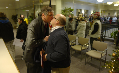 Steve Griffin  |  The Salt Lake Tribune   Gage Church, left,  and Tim Sharp kiss after receiving their marriage license at the Weber County Clerk's Office in Ogden, Utah Monday, December 23, 2013.